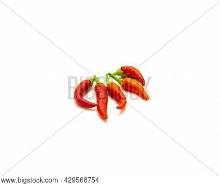 Organic Pile Of Red Thai Hot Chili Peppers Isolated On White Background