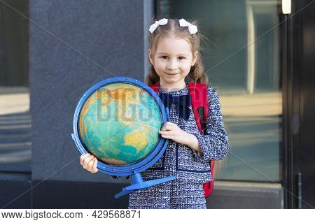 Beautiful Kid Back To School. Happy Cute Clever Confident Girl With In Blue Uniform Go To First Grad