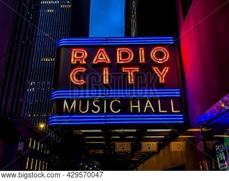 Radio City Music Hall Marquee Neon Sign In Nyc During Twilight Hours Near Buildings In Background. T