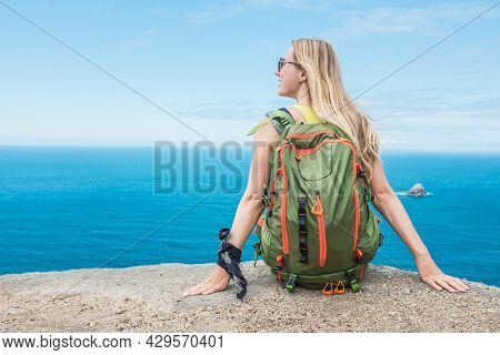 Woman hiker, hiking backpacker traveler camper  on the top of mountain in sunny day under sun light. Beautiful sea landscape view.
