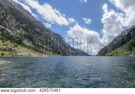 Mountain Lake In The Pyrenees With The Cavallers Dam In The Background And High Mountains On The Sid