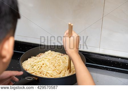Kid Cooking A Healthy Italian Spaghetti With Smashed Pork At Home