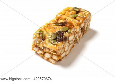 Sweet Caramel Treats With Raisins And Melon Seeds On White Background