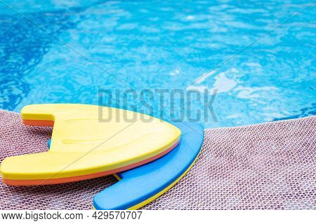 Yellow And Blue Floating Pads Near A Swimming Pool