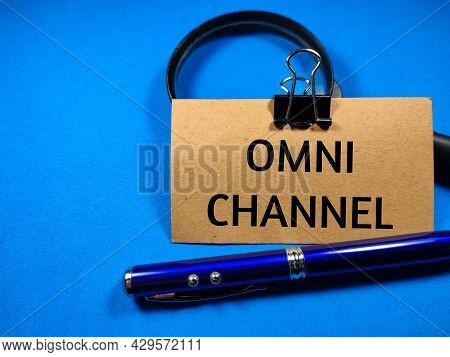 Business Concept.text Omni Channel Writing On Brown Card With Pen And Magnifying Glass On A Blue Bac