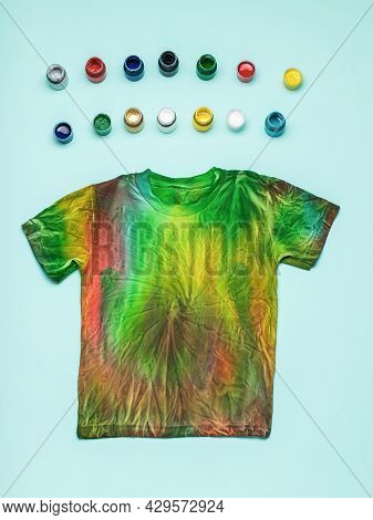 Small Jars Of Colored Fabric Dyes And A Tie Dye T-shirt On A Blue Background. Coloring Clothes By Ha