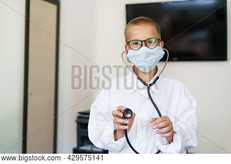 Portrait Of A Caucasian Male Child In A Doctors Robe With A Phonendoscope, In Hand And Glasses. Play