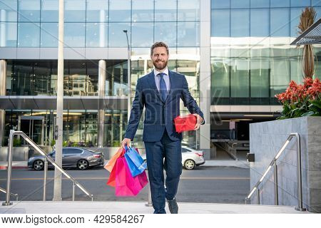 Happy Entrepreneur In Businesslike Suit With Shopping Bags Gifts Walk Outside The Office, Mens Day