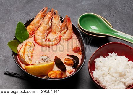 Traditional Thai soup Tom Yum kung with seafood, coconut milk and chili pepper and rice bowl