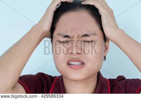 Close Up Of Pretty Asian Woman Closing Eyes And Clasping Her Head In Worry About Problems, Feeling C