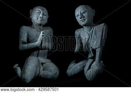 Buddhist Monks In Peaceful Meditation. Traditional Vintage Thai Buddhism Statues. Old Wood Carvings