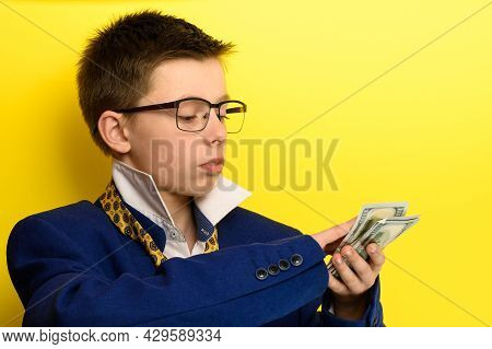 The Guy In An Adult Suit Waves American Dollars, A Portrait Of A Child On A Yellow Background.