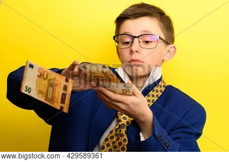 The Child Scatters Money, A Boy In A Suit Throws Euros, A Portrait Of A Child On A Yellow Background
