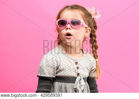 Cute And Little Girl On A Pink Background, Long Pigtails And A Gray Dress, A Girl With Glasses.