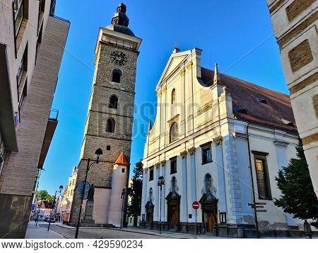 Ceske Budejovice, Czech Republic - July 12, 2021: Baroque Black Watchtower With A Christian Church O