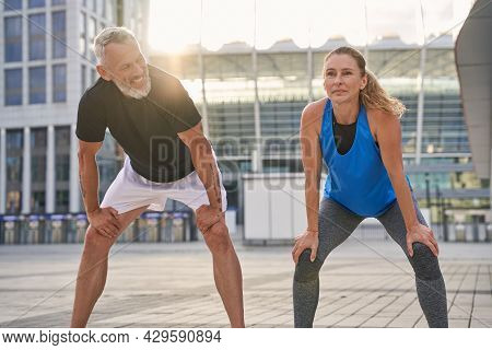 Active Sporty Middle Aged Couple, Man And Woman Prepared For Running Together In The City On A Summe