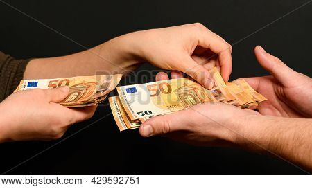 People Count Money, Counting Euro Bills By Man And Woman, Money On Black Background.