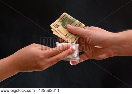 Drug Dealer Passes A Dose To A Merchant, Sachets Of Powder On A Black Background.