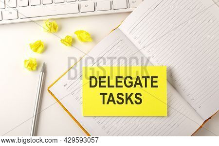 Delegate Tasks Text On Sticker On Diary With Keyboard And Pencil