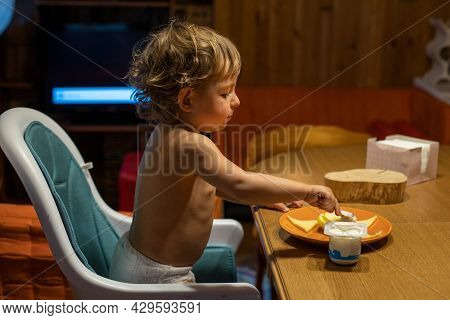Cute Caucasian Baby Eating At The Table. Toddler Eatts By Himself At The Adult Table