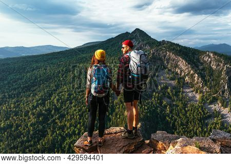 A Traveling Couple In Hiking Gear In The Mountains At Sunset. Two Tourists On The Top Of The Mountai