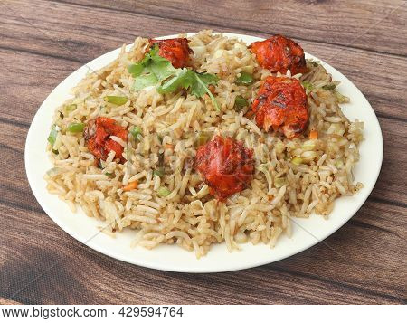 Veg Manchurian Fried Rice, Made Of Fried Mixed Vegetables Balls Along With Rice Is Tossed In Soy Tom
