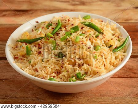 Healthy And Tasty Malaysian Veg Fried Rice Served In Bowl Over A Rustic Wooden Background, Selective