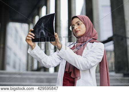 X-ray, Roentgen Image. Serious Thoughtful Muslim Woman Surgeon, Looking At X-ray Radiography Of Pati