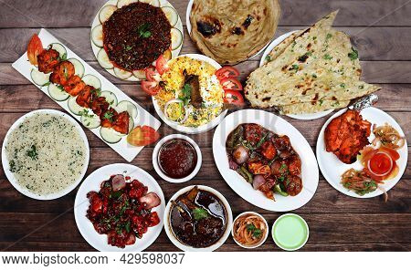 Assorted Indian Food On Wooden Background. Chicken Tikka, Chicken Briyani, Chilli Chicken, Chicken M