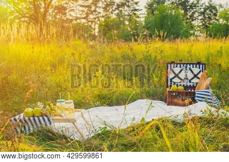 Summer Picnic At Sunset. A Beautiful Equipped Picnic Area With All The Accessories. A Wicker Picnic