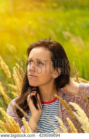 Portrait Of A Brunette Girl In A Knitted Cardigan Standing In A Field, A Light Breeze And Sunlight