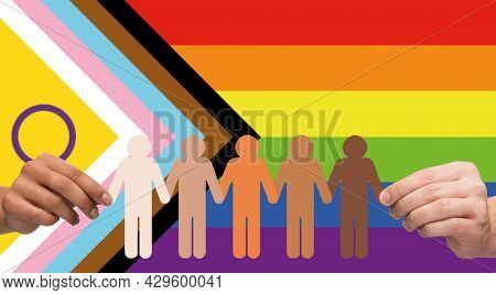 lgbtq, trans and intersex rights concept - multiracial couple hands holding paper chain of people pictogram over progress pride flag on background
