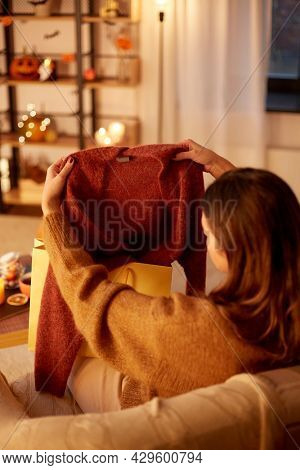 halloween, holidays and leisure concept - young woman taking woolen cardigan from shopping bag at cozy home