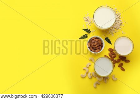 Different Vegan Milks, Oat Flakes And Nuts On Yellow Background, Flat Lay. Space For Text