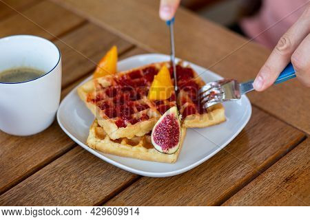 Waffles For Breakfast With Jam. Homemade Waffles With Berries In A Plate On A Wooden Table. A Man Ea