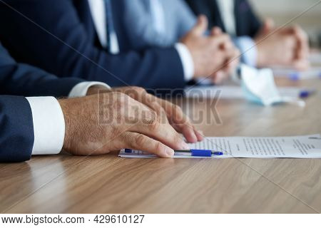 A Man In An Elegant Suit Holds His Hands On The Table, Next To A Document, During A Work Meeting. Wi