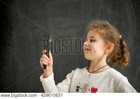 Little Girl Looks Through The Magnifying Glass On A Gray Background. High Quality Photo