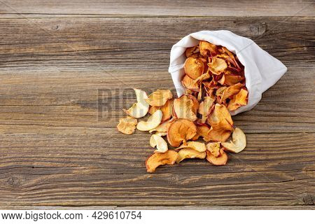 A Pile Of Dried Slices Of Apples Pills Out Of A White Pouch On Wooden Background. Dried Fruit Chips.