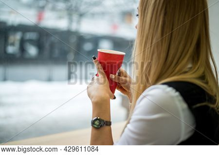 Beautiful Blonde Girl Drinks Coffee In The Cafe.