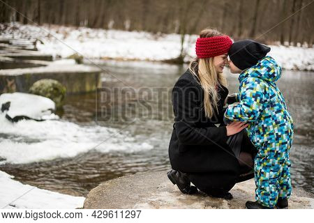 Young Mother With Her Son In Winter On A Lake.