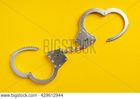 Opened Handcuffs On Yellow Background. Release From Prison, Freedom Concept. Imprisonment, Deprivati
