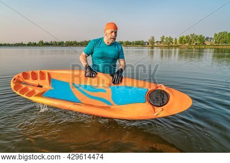 athletic, senior man with a prone kayak on a lake in Colorado, this water sport combines aspects of kayaking and swimming
