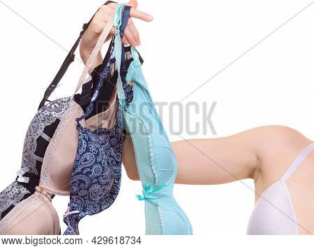 Bosom Concept. Slim Young Woman Wearing Underwear Holding Different Color Bras In Hand, Choosing Whi