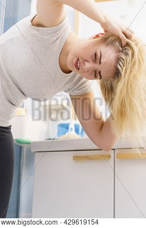 Blonde Woman Having Problems With Greasy Oily Hair In Bathroom. Female Showing Scalp, Scratching Her