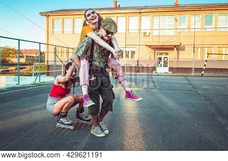 Group Of Friends Hanging Out Outside. One Girl Back Riding Her Friend, Other Rides Behind On Rollers