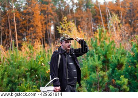 A Man In The Forest, A Hunter, A Mushroom Picker In A Military Cap Stands In The Forest And Points T