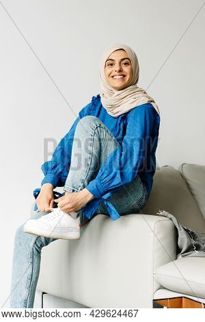 Smiling young arab woman wearing hijab tying shoelace sitting on a couch at home