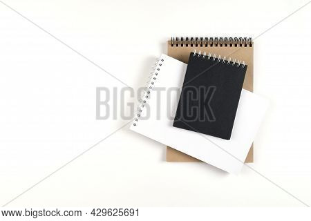 Three Blank Notepads On A Spiral Stacked In A Stack On A White Background. Notebooks With White, Bla