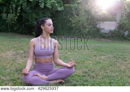 Young Woman Relaxing In Yogla Lotus Pose At Garden, Outdoors, Eyes Closed