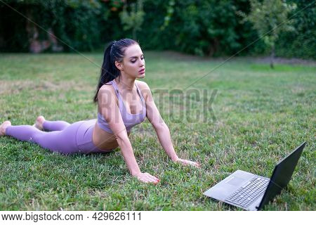 Young Woman Stretching Body And Watching Tutorial Video By Laptop Outdoors In Garden